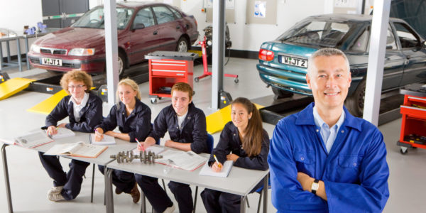 Mechanic with students studying automotive trade in college garage smiling at camera